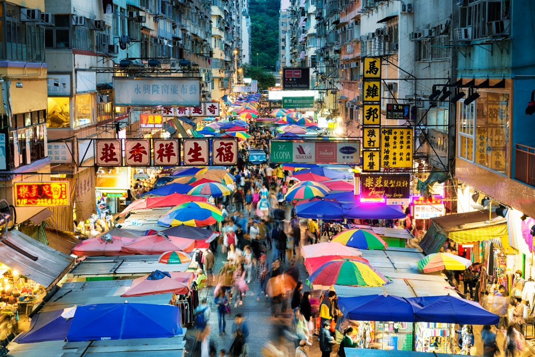 Colourful tents and neon lights surround the night market in between tall apartment buildings
