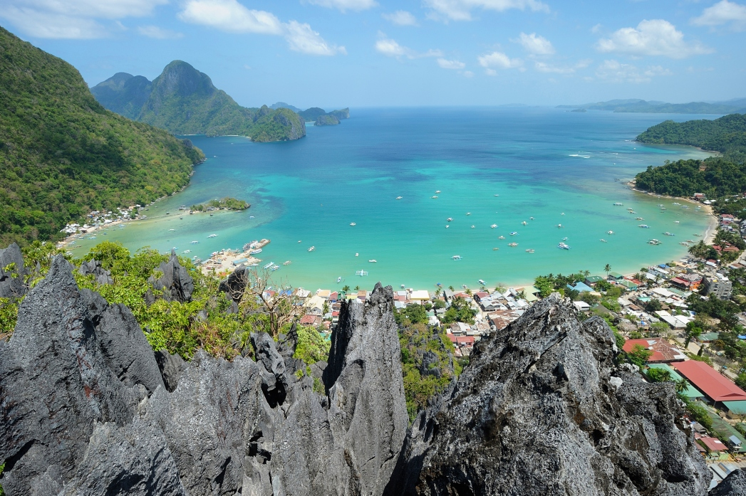 A turquoise bay with a sandy beach and some cliffs in Palawan.