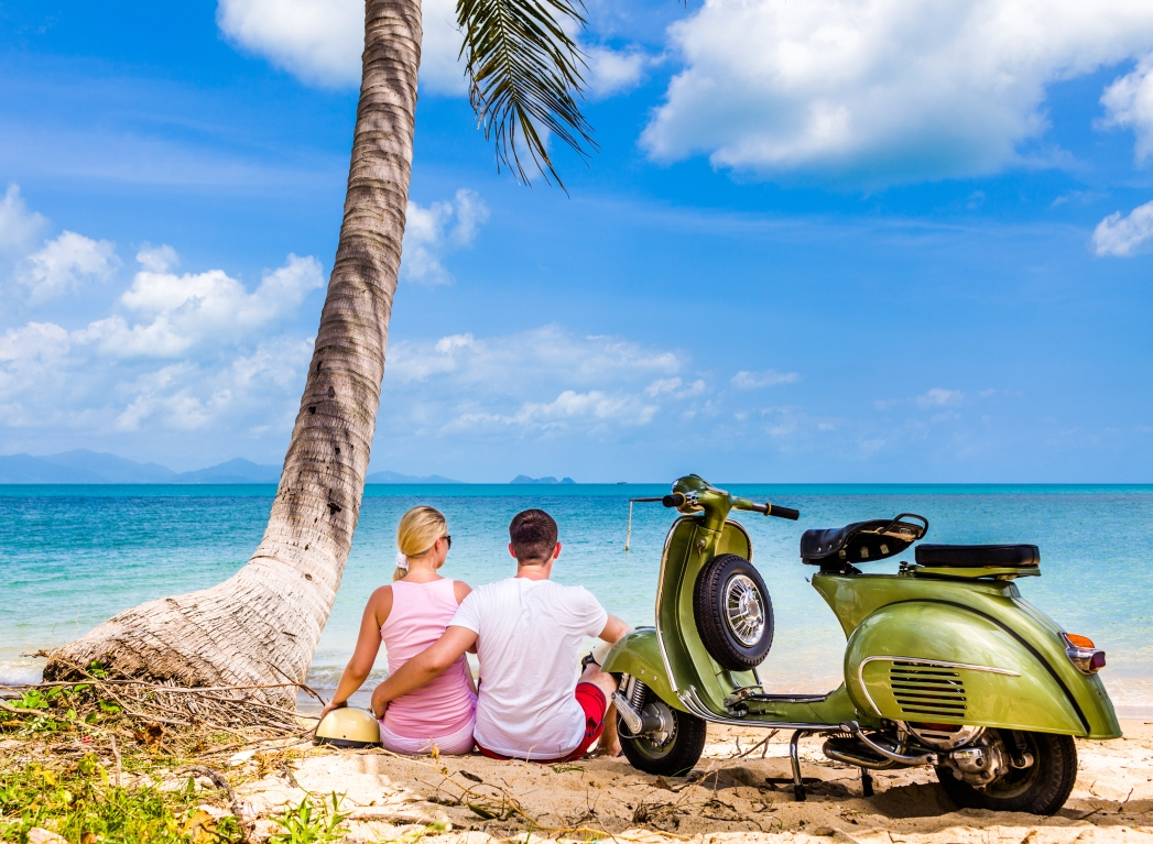 A couple sitting on a beach in front of a scooter