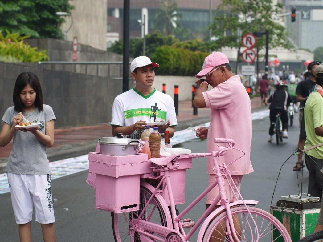 Man in pink selling street fare
