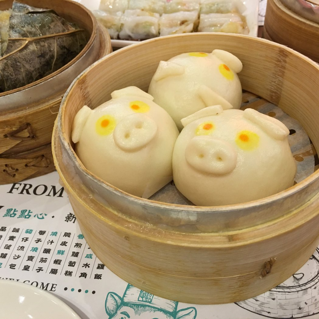 Three pig-shaped buns rest snugly in a round bamboo steamer.