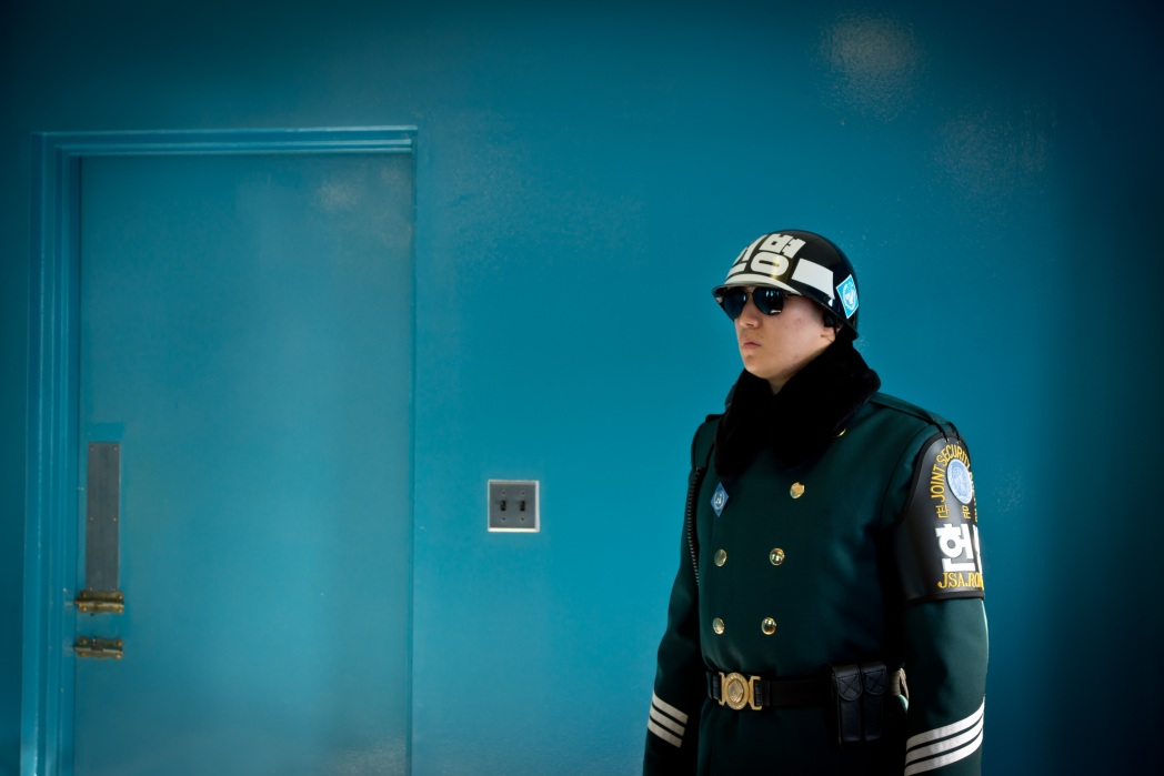 Soldier in uniform waiting by blue walled building