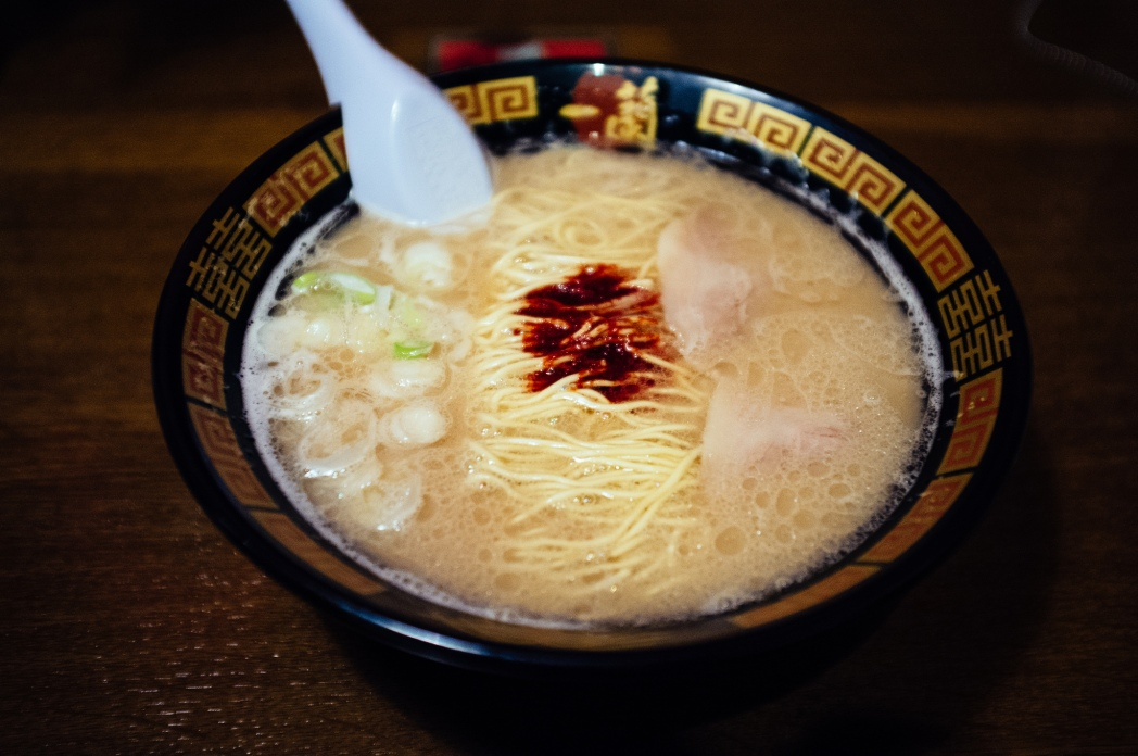 A bowl of ramen with a spoon on the side.
