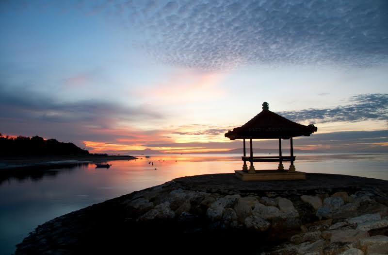 Bali beach at sunset with clear gradation blue sky and some tints of orange