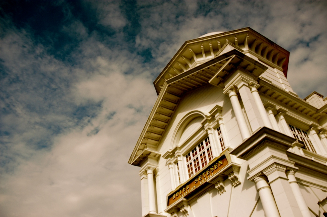 Colonial building with cloudy sky behind