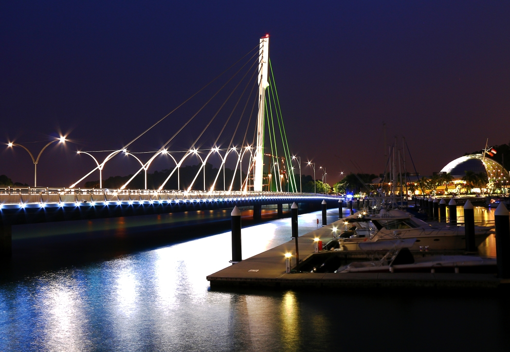 Keppel Bridge lit up at night, alongside peaceful boats and yachts docked in the bay.