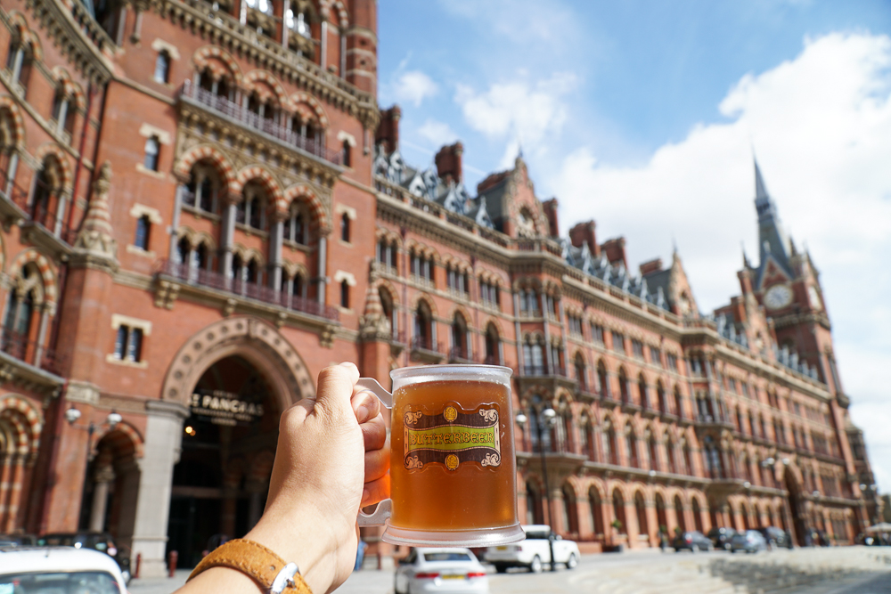 A mug of butterbeer against the view of St. Pancras International