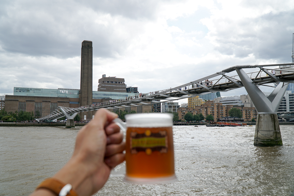 A mug of butterbeer against the view of London's Millennium Bridge