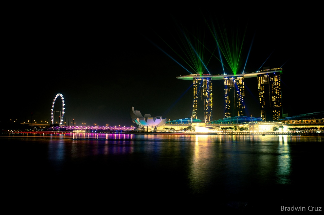 Laser lights shine from the Marina Bay Sands across the Singapore night sky.