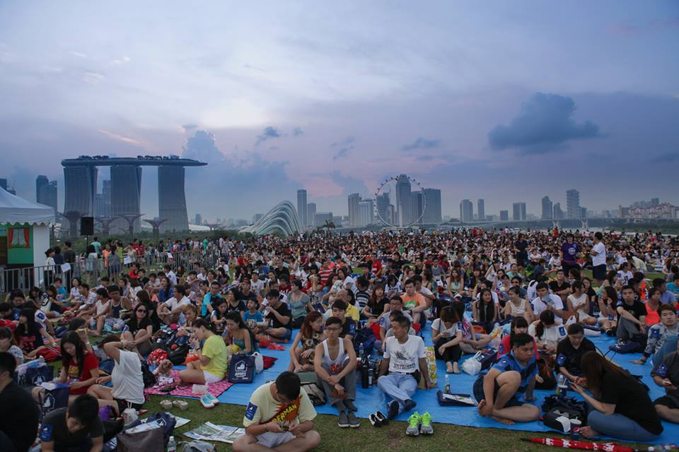 Movie-goers spread out across the lawn as far as the eye can see, waiting for the movie to begin at dusk