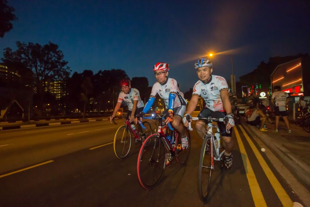 Cyclists riding together in a group on the roads of Singapore at night.