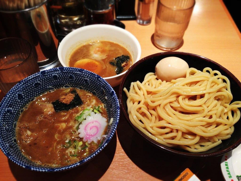 A bowl of savoury broth on the left, and a bowl of dry noodles and an egg on the right.