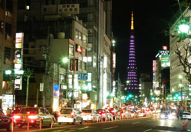 A view of cars and lit up buildings in Roppongi at night.