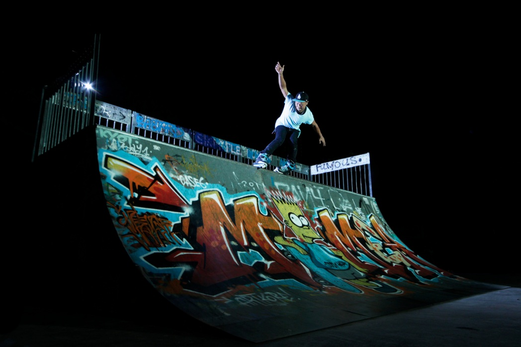 A skateboarder at Somerset Skate Park at night