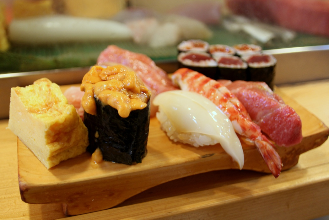 Nigiri sushi on a wooden plate, set on a counter.