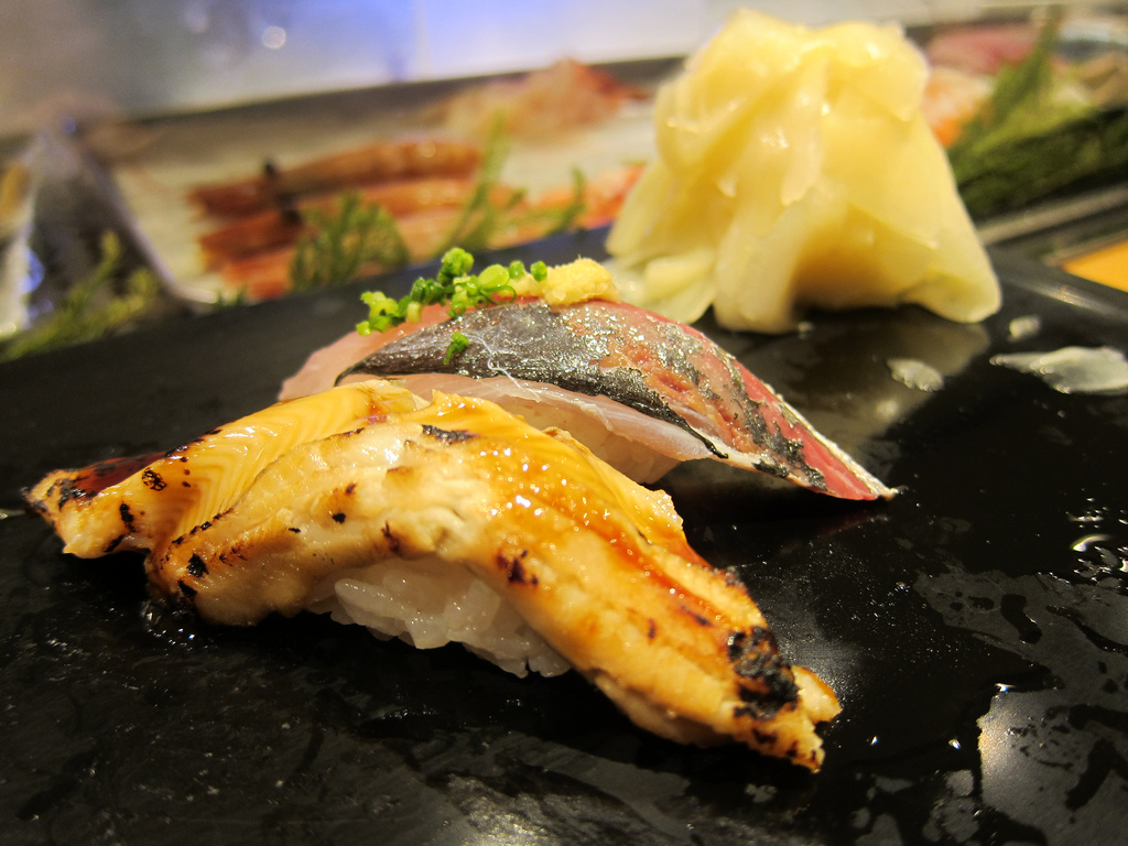 Two glimmering pieces of charred fish nigiri rest on a black plate.
