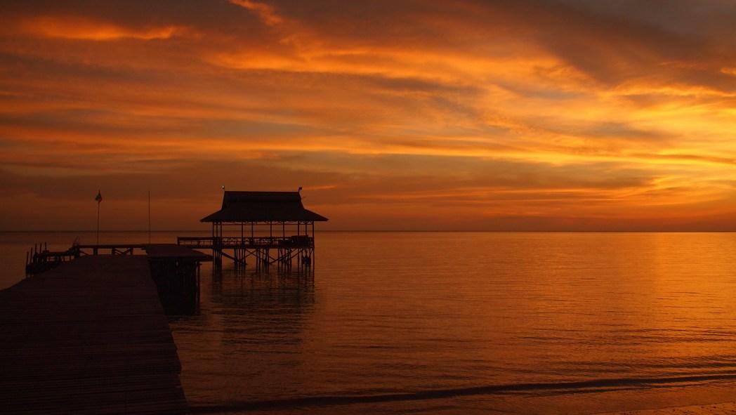 Orange sunset at beach with pier